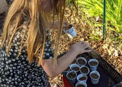 girl filling cups with dirt in garden